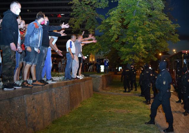 Демонстранты жестикулируют в адрес ОМОНа во время акции протеста после закрытия избирательных участков на президентских выборах в Беларуси, в Минске 9 августа 2020 г.