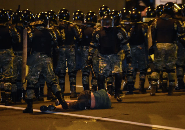 Мужчина лежит на земле перед ОМОНом во время акции протеста после закрытия избирательных участков на президентских выборах в Беларуси в Минске 9 августа 2020 г.