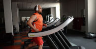 Мужчина во время тренировки на беговой дороже в спортзале. Архивное фото