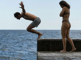 Мужчина прыгает с пирса на пляже в Крыму