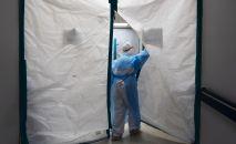 Медицинский работник в защитном костюме входит в палату больницы. Архивное фото