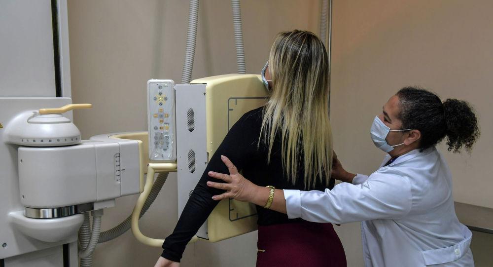 Медицинский работник проводит пациента на рентген грудной клетки. Архивное фото