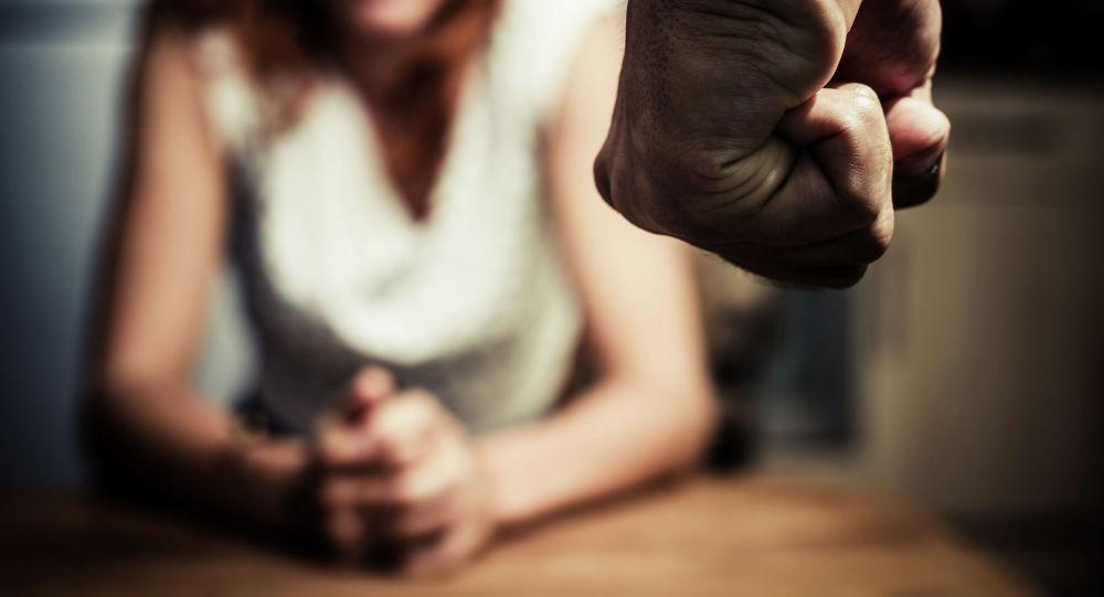 Кулак мужчины на фоне женщины сидящей на стуле. Иллюстративное фото