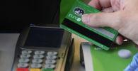 Посетитель расплачивается банковской картой. Архивное фото