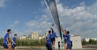 Молодые парни играют в волейбол в новом парке в южной части Бишкека