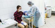 Девушка сдает тест на наличие антител к коронавирусу. Архивное фото