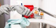 Женщина в перчатках убирается на кухне. Иллюстративное фото