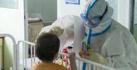 Медик с юным пациентом с коронавирусной инфекцией COVID-19. Архивное фото