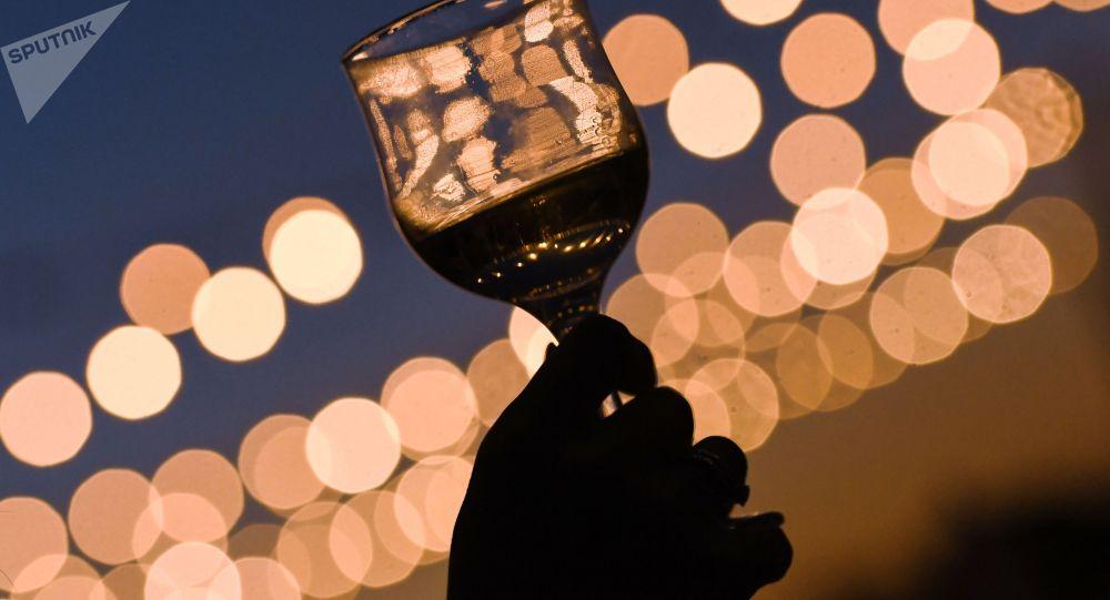 Человек держит бокал с вином на праздничном торжестве. Архивное фото