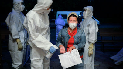 Медицинский работник дезинфицирует руки пациента, подозреваемого на коронавирус, когда она входит в зал ресторана, который был преобразован в ночную клинику в Бишкеке. Кыргызстан, среда, 22 июля 2020 года