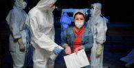 Медицинский работник дезинфицирует руки пациента, который входит в ночной стационер в Бишкеке. Архивное фото