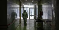 Медицинский работник в защитном костюме гуляет в зоне неотложной помощи государственной больницы доктора Альберто Антраника Эрнекяна в Эсейсе на окраине Буэнос-Айреса. 1 июля 2020 года