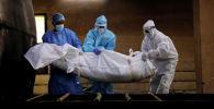 Медициналык кызматкерлер COVID-19дан каза болгон адамдын өрттөө үчүн көтөрүп жатышат. Архив
