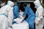Медицинские работники с телом человека, умершего от COVID-19