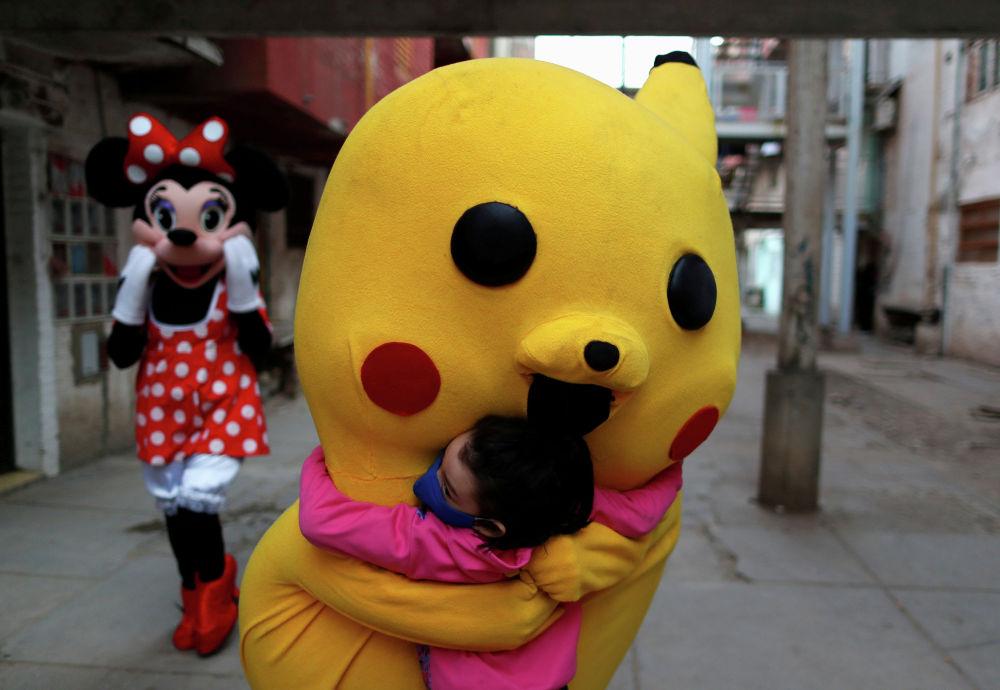 Аниматор в образе Пикачу приветствует ребенка в День защиты детей в Буэнос-Айресе.