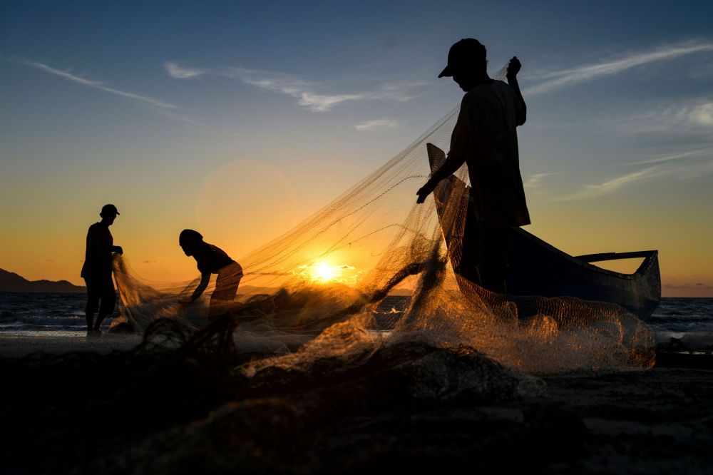 Рыбаки в Индонезии чистят сети после выхода в море.