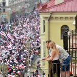 Пара смотрит на демонстрантов с балкона во время марша сторонников оппозиции в знак протеста против результатов президентских выборов в Минске. 23 августа 2020 года