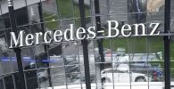 Логотип компании Mercedes-Benz на фасаде автосалона. Архивное фото