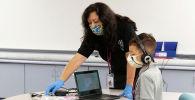 Преподаватель помогает ученику в начальной школе Уилсона в Фениксе в штате Аризона. Архивное фото