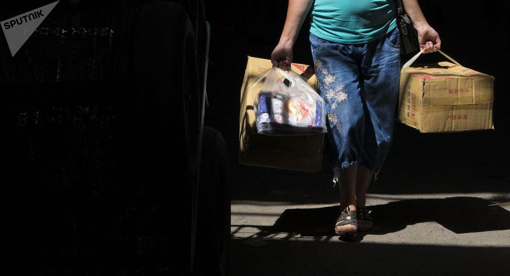 Женщина несет коробки на рынке. Архивное фото