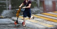 Женщина переходит через дорогу во время дождя. Архивное фото