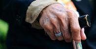 Пожилой мужчина держится за трость. Архивное фото