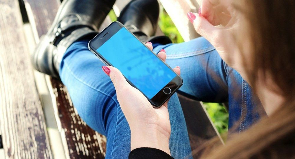 Девушка с телефоном в руке. Архивное фото