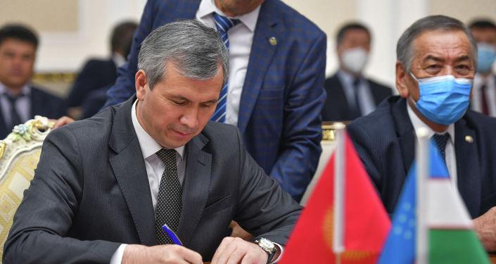 Вице-премьер-министр Акрам Мадумаров подписывает протокол после переговоров правительственных делегаций Кыргызстана и Узбекистана по делимитации и демаркации кыргызско-узбекской государственной границы