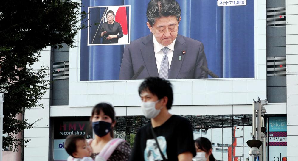 Люди в защитных масках проходят мимо большого экрана, на котором транслируется пресс-конференция премьер-министра Японии Синдзо Абэ в Токио. Архивное фото