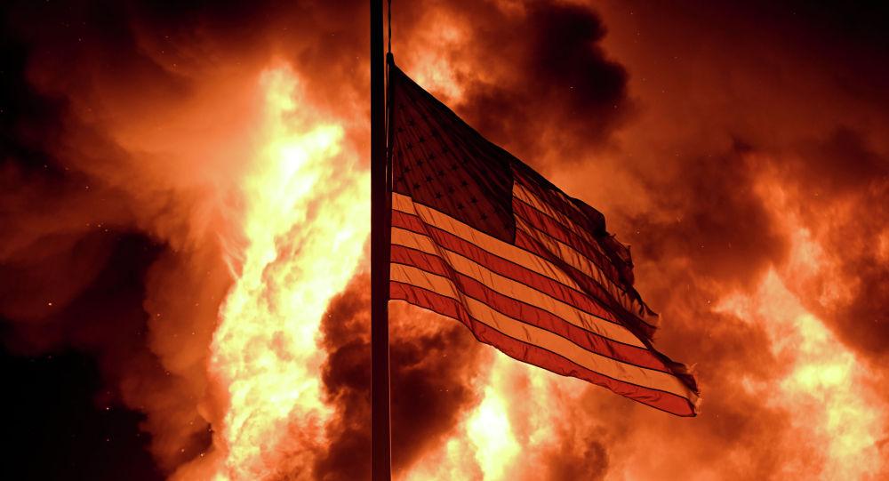 Флаг США на фоне пожара в здании Управления исправительных учреждений города Кеноша. Архивное фото