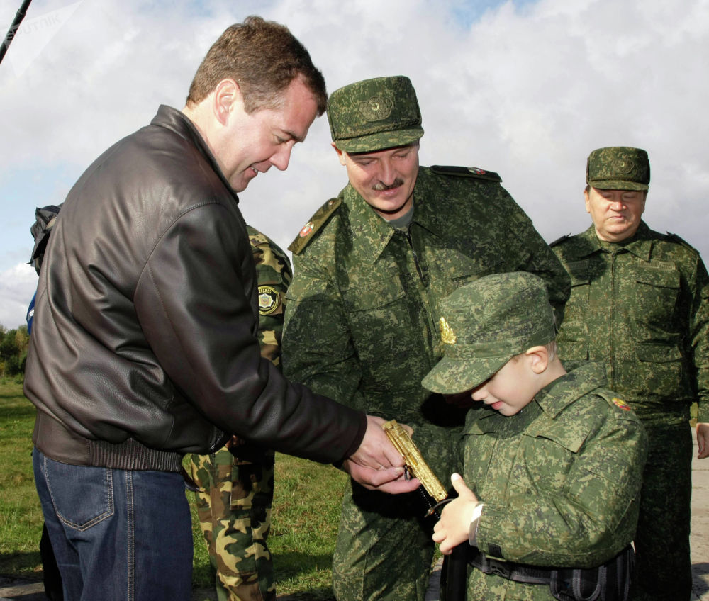 Ошол кездеги Россиянын президенти Дмитрий Медведев кичинекей Коляга алтын түстүү тапанча тапшырууда