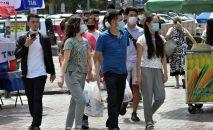 Молодые люди в масках идут по одной из улиц Бишкека. Архивное фото