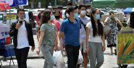 Молодые люди в масках идут по уличному рынку в Бишкеке. Архивное фото