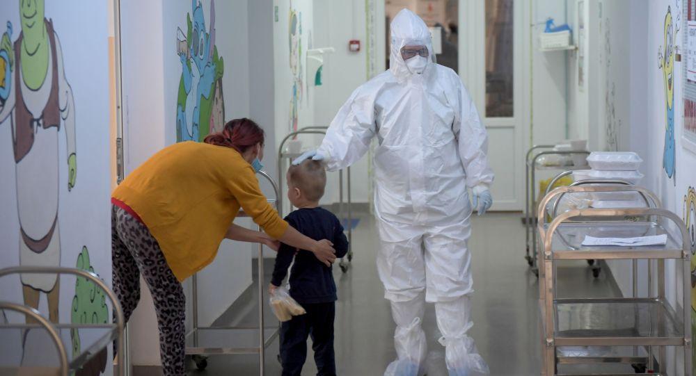 Медперсонал инфекционной больницы утешает ребенка, инфицированного COVID-19. Архивное фото