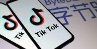 Логотипы TikTok на смартфонах перед логотипом ByteDance. Архивное фото