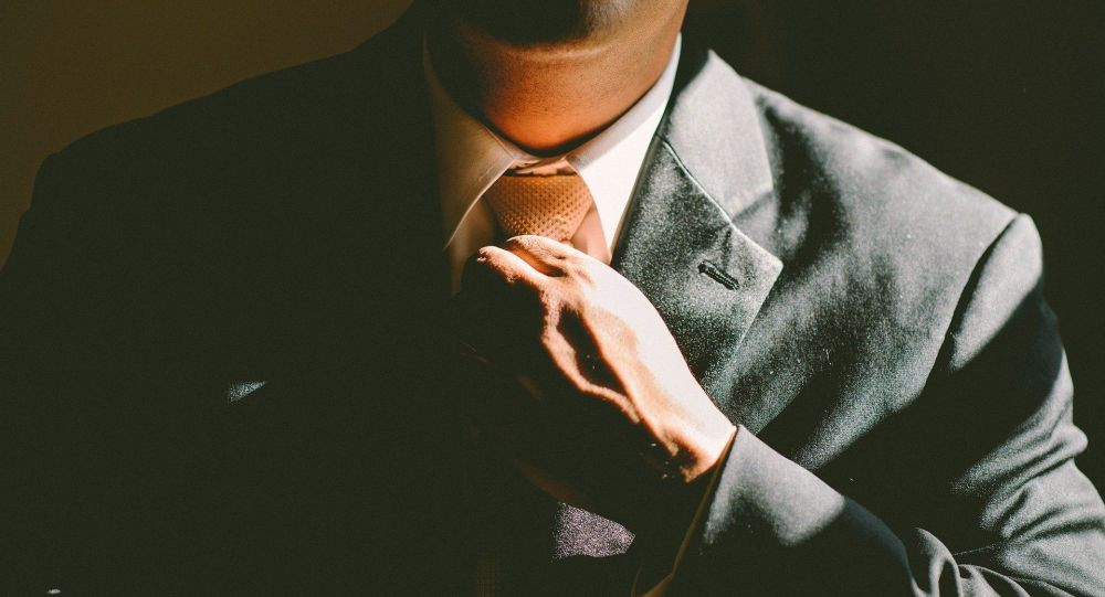 Киши галстукту байлап жатат. Архив