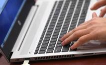 Человек за ноутбуком во время работы. Архивное фото