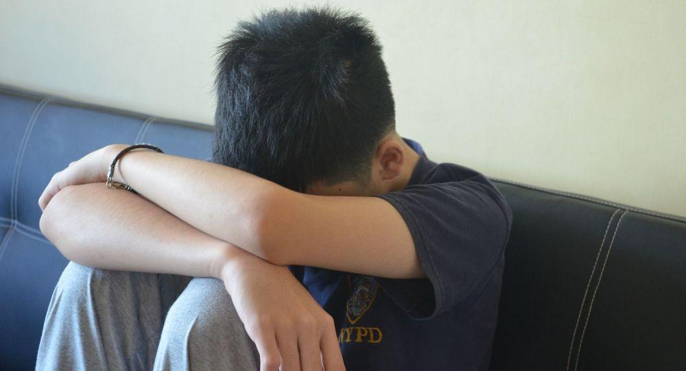 Подросток сидит склонив голову. Иллюстративное фото