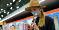 Девушка на платформе метрополитена со смартфоном в руках. Архивное фото