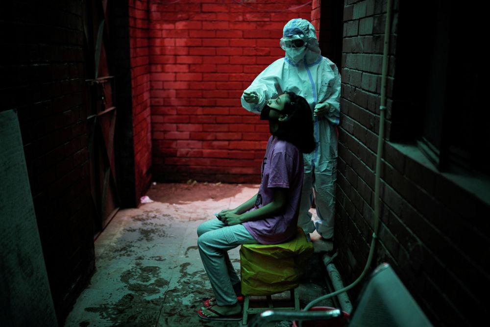 Медицинский работник в средствах индивидуальной защиты (СИЗ) собирает образец с помощью мазка у человека в местном медицинском центре для проведения тестов на коронавирусную болезнь (COVID-19) на фоне распространения болезни в Нью-Дели, Индия, август. 31 января 2020 года.