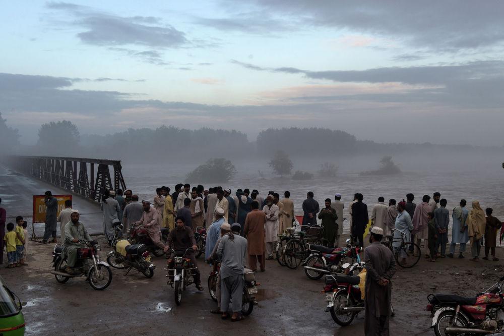 Местные жители собираются, чтобы посмотреть, как разлившаяся река Чарсадда течет под мостом после сильных муссонных дождей на окраине Пешавара 2 сентября 2020 г.