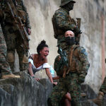 Женщина плачет рядом с телом супруга, который был застрелен во время полицейской операции после ожесточенных столкновений между бандами наркоторговцев в Рио-де-Жанейро (Бразилия)