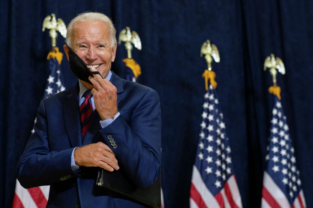 Кандидат в президенты от демократов, бывший вице-президент Джо Байден улыбается, надевая маску после разговора со СМИ в Уилмингтоне, штат Делавэр, в пятницу, 4 сентября 2020 г.