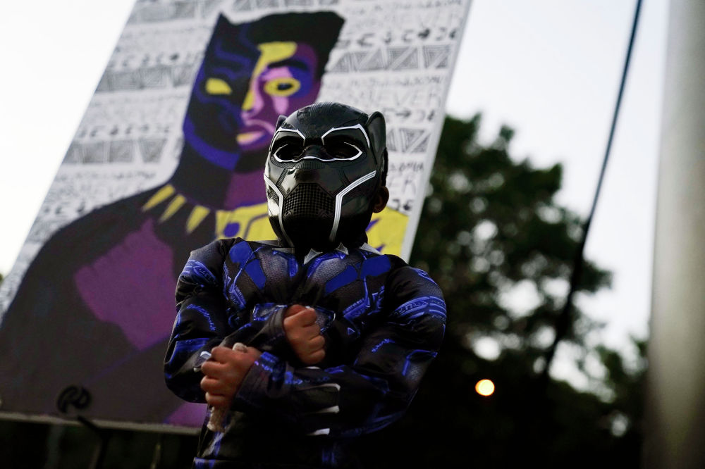4-летний Мейсон Уилкс из Южной Каролины позирует своему отцу в костюме Черной пантеры в дань уважения актеру Чедвику Боузману, который скончался в возрасте 43 лет от рака толстой кишки.