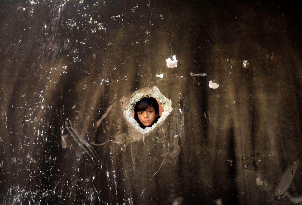 Палестинский ребенок проверяет дом, который загорелся, унеся жизни троих детей после того, как огонь был зажжен свечой, использованной для освещения их комнаты во время отключения электроэнергии в лагере беженцев Аль-Нусират в центре сектора Газа 2 сентября 2020 года.