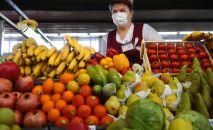 Продавщица на рынке продает фрукты. Архивное фото