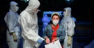 Женщина в медицинской маске входит в ночной стационар, где оказывается помощь пациентам с COVID-19. Архивное фото