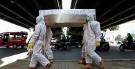 Государственные служащие в защитных костюмах несут макет гроба жертвы коронавируса COVID-19, чтобы предупредить людей об опасностях болезни, Джакарта, Индонезия
