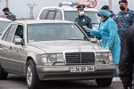 Медицинский работник проверяет температуру у водителя с армянскими номерами на КПП. Архивное фото