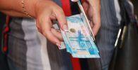 Женщина с деньгами в руке. Архивное фото